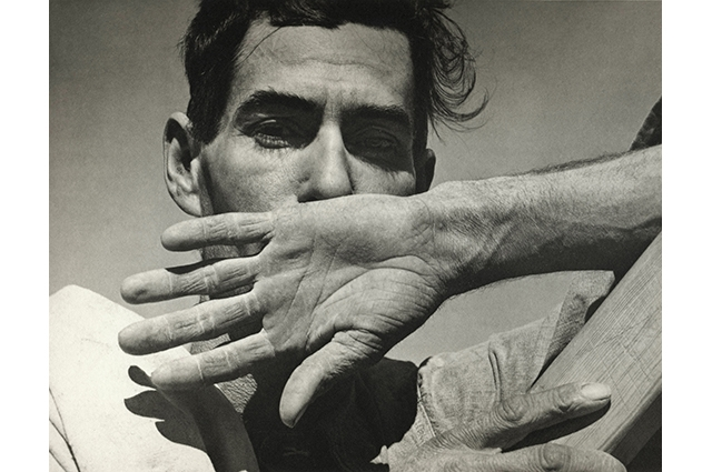 Black and white close up image of a man with his hand covering his mouth