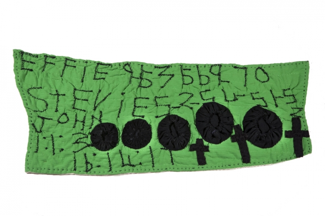 "Pieced by Rosie Lee Tompkins, Quilted by Irene Bankhead, Black yo-yo's on green hanging (Stevie). 16 in. high x 38"" in. wide. Collection of Eli Leon. Photo: Terry Lorant"