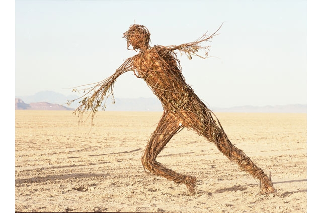 A hay sculpture of a man running in the desert