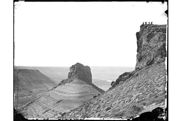 Black and white image a vast desert landscape with a group of people standing on a rock in the distance
