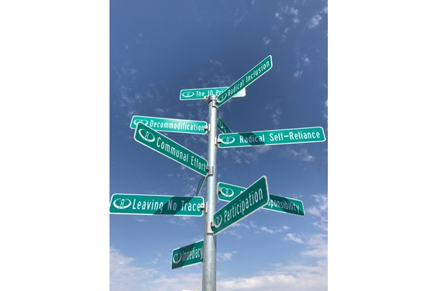 A large street sign with 10 signs, with the visible signs reading: Radical Inclusion, Decommodication, Radical Self-Reliance, Communal Effort, Leaving No Trace, Participation, Immediacy
