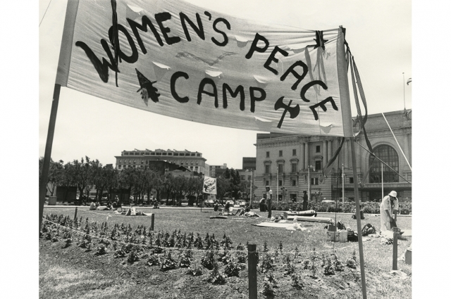 A black and white image of a large sign reading: WOMEN'S PEACE CAMP