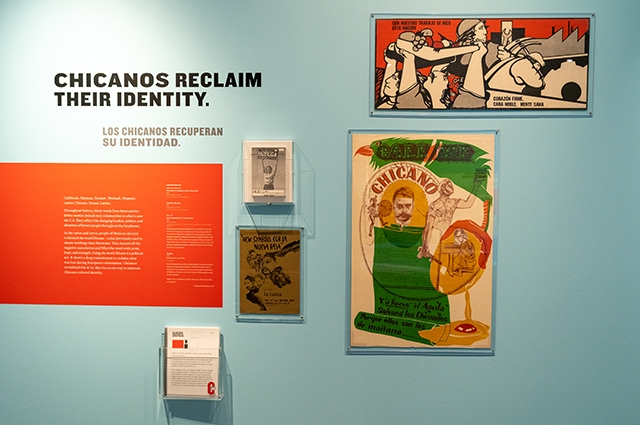A section of the exhibition reading: Chicanos Reclaim Their Identity. Features multiple posters and text.