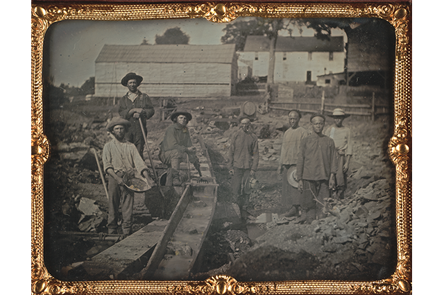 Black and white image of a group of men working on a field
