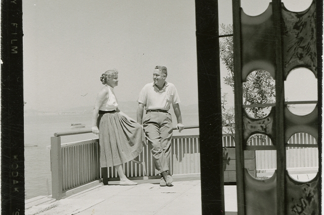 Black and white photograph of Edith Heath and her husband talking on their deck.