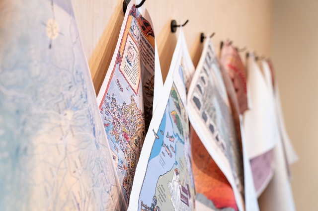 Large colorful maps hanging on the wall inside the exhibition