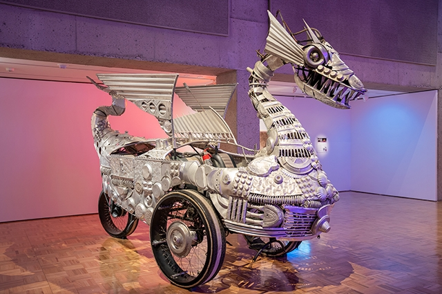 A large silver 3-wheeled vehicle sculpture with a dragon's head at the front, wings on the side, and a tail in the back