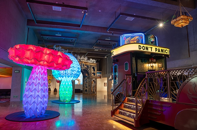 Two large, multicolored mushroom-shaped sculptures and a large mobile theater with a marquee reading: Don't Panic