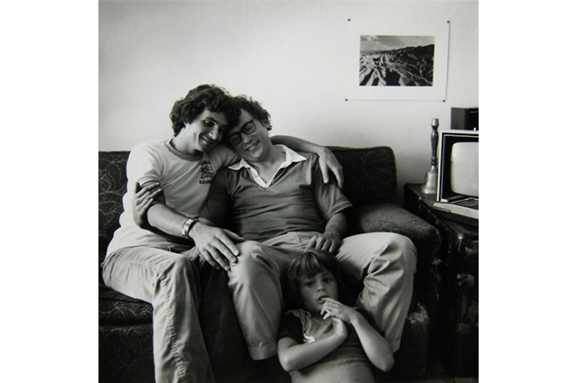 A black and white image of two men embracing on the couch while a young boy sits between them on the floor