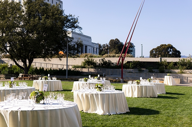White table settings are set up in the OMCA garden for a wedding.