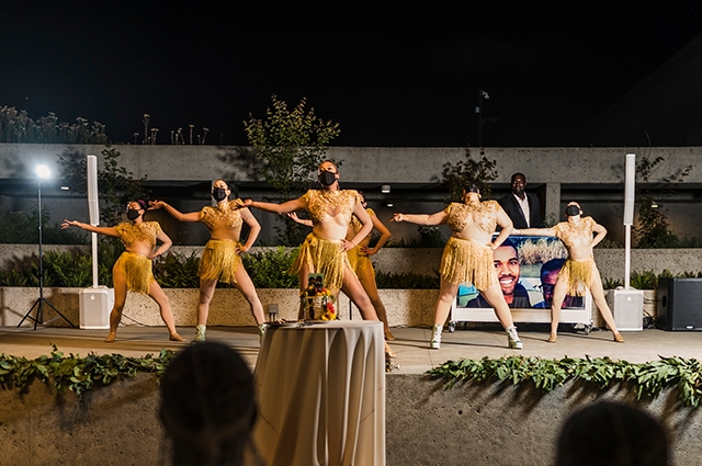 Dancers wearing shimmery gold outfits perform on the OMCA garden stage.