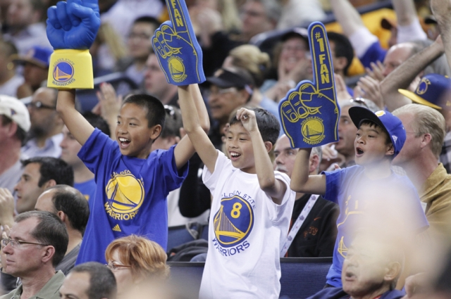 Golden State Warriors fans cheering courtside. Courtesy of Visit Oakland