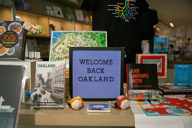A table display at the OMCA store features Oakland-related items.