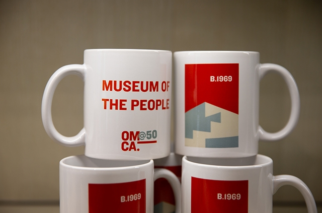 A stack of red and white OMCA mugs at the museum store.