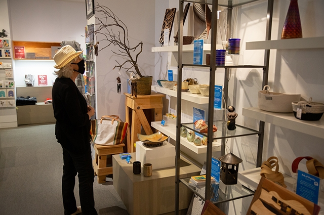 A woman wearing a mask and sunhat browses the OMCA store shelves.