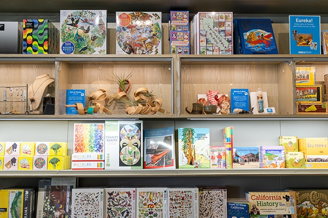 Image of shelves of merchandise like artful planters, books, and other items inside the OMCA Store