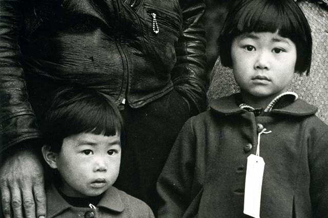 Black and white image of two children with tags on their coats