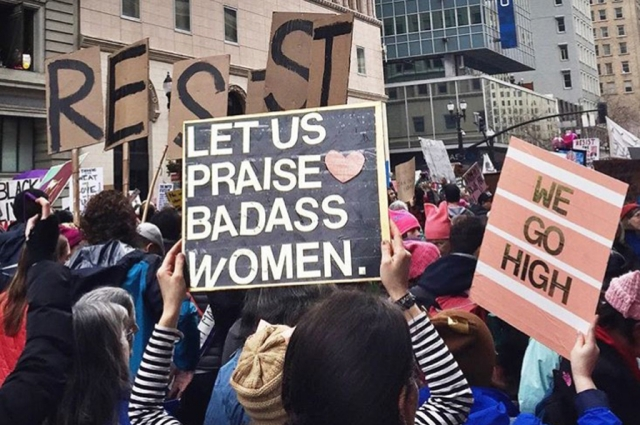 "Photo with signs reading ""Let us now praise badass women."" Photo: Anna Samuelson"