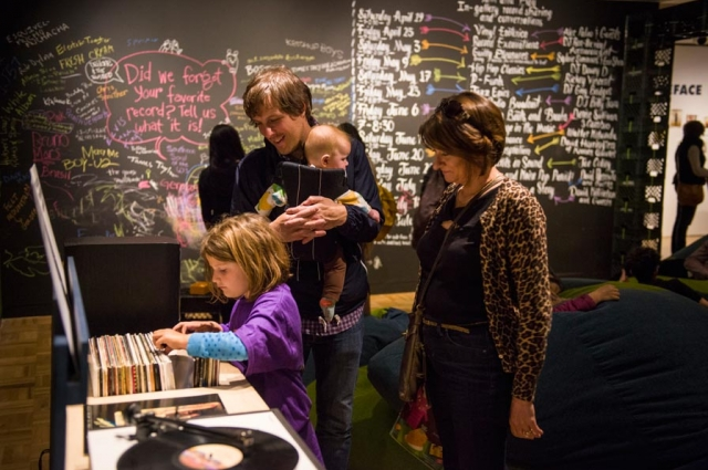 A family explores a crate of records selected especially for group listening in the exhibition Vinyl: The Sound and Culture of Records. Photo: Shaun Roberts.