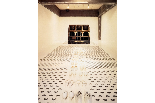 A long white hallway with a large brown shoe shine stand at one end with white tap shoes and silver taps lining the hallway