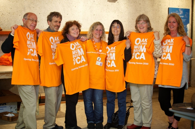 Volunteers hold up their OMCA t-shirts with smiles