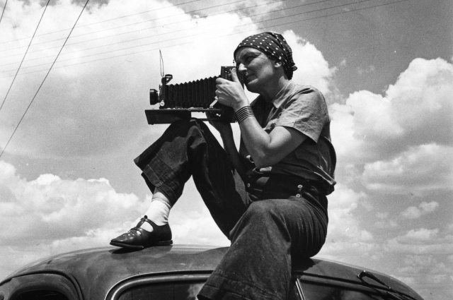 Dorothea Lange holding a camera sitting on top of a car