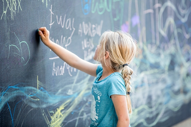 Girl draws on chalkboard
