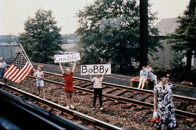 Children hold an U.S. flag and signs that say Goodbye Bobby