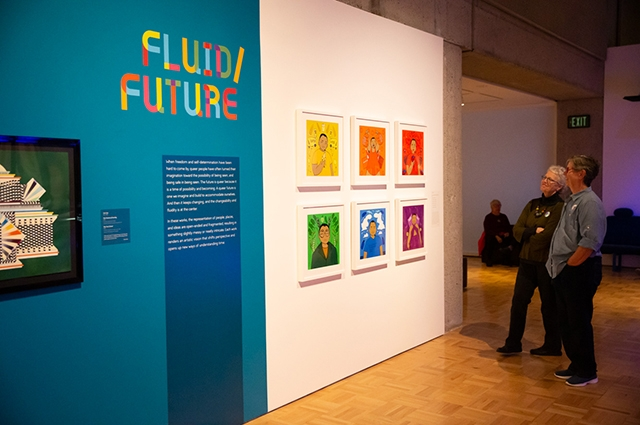 Two women smile and look at a blue wall with 6 colorful paintings and text that reads: Fluid/Future