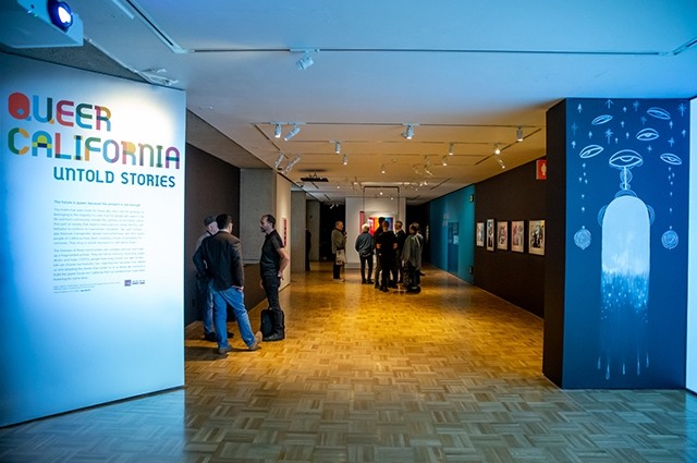 Entryway to Queer California exhibition. The left wall has the title and description of the exhibit while the right wall is black with white drawings