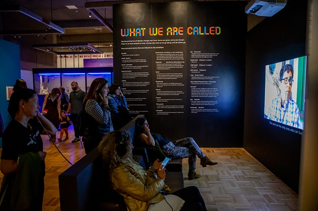 A group of people sit and watch a video and a wall in the background reads: What We Are Called
