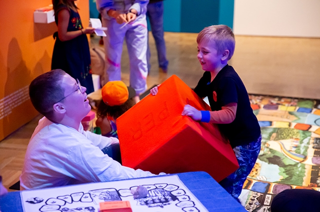 A person plays with a child and a soft red cube inside Queer California
