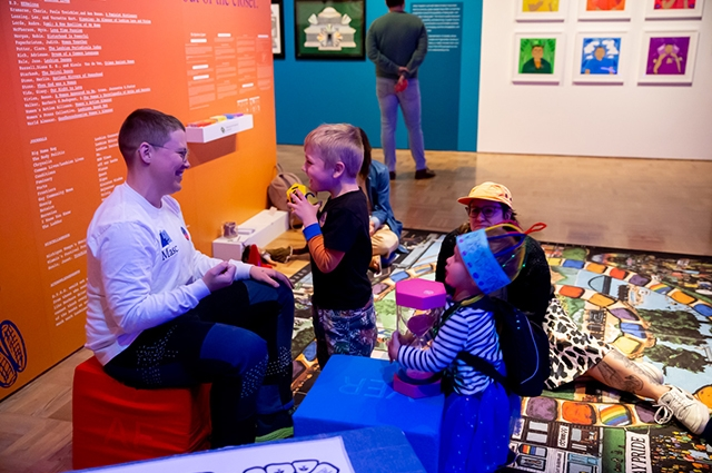 A family smiles and holds game pieces inside the Gaymes Lounge in Queer California