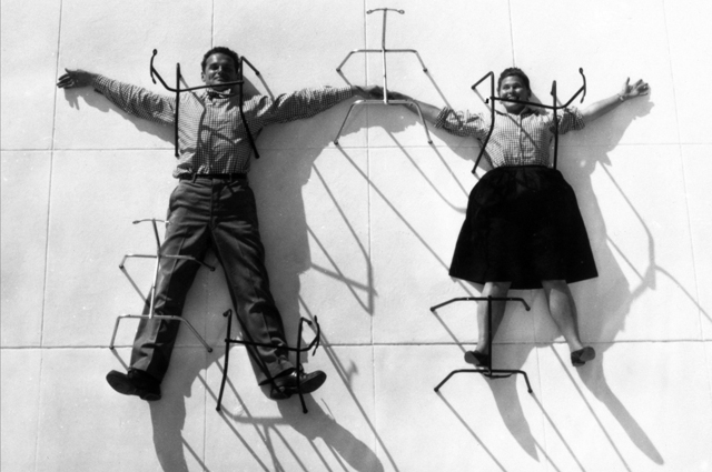 Charles and Ray Eames posing with chair bases. © Eames Office LLC.