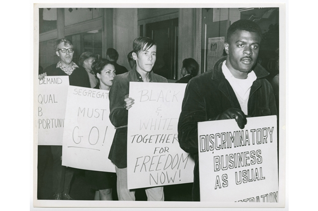 Ablack and white image of people protesting with signs that read: 'Black & white together for freedom Now!' and 'Discriminatory business as usual'