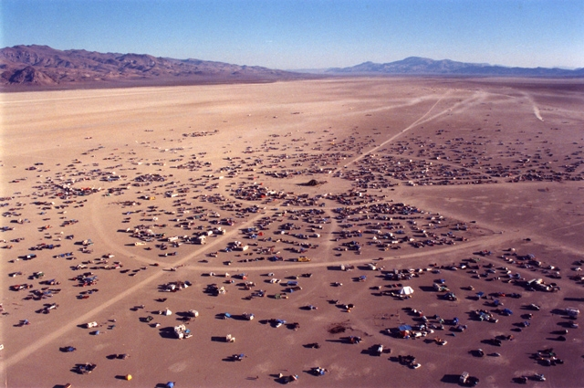 An aerial shot of Black Rock City, a desert landscape with many tents formed in concentric circles
