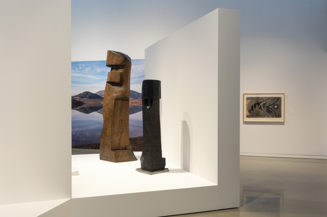 Two sculptures by J.B. Blunk inside the gallery with an image in the background of Inverness