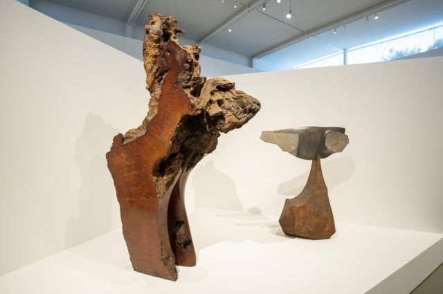 Two wood and stone sculptures inside of the gallery by J.B. Blunk