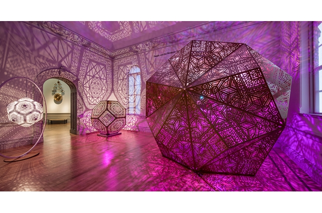 Three sculpture pieces that light up pink and fill a room with geometric shadows