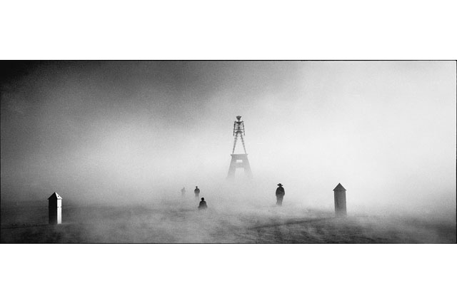 A black and white image of the Burning Man amidst fog and men viewing the statue
