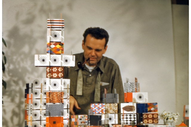 Charles Eames with a pipe sticking out of his mouth building a large house of cards