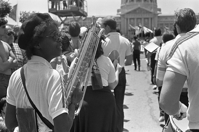Black and white image of a Black woman with a glockenspiel in a marching band