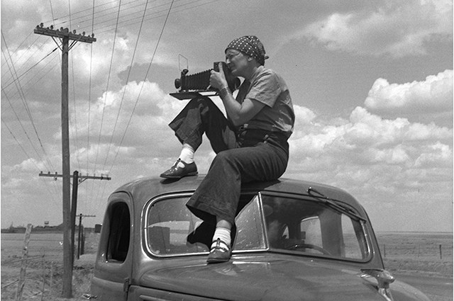 Dorothea Lange with a camera sitting on a car