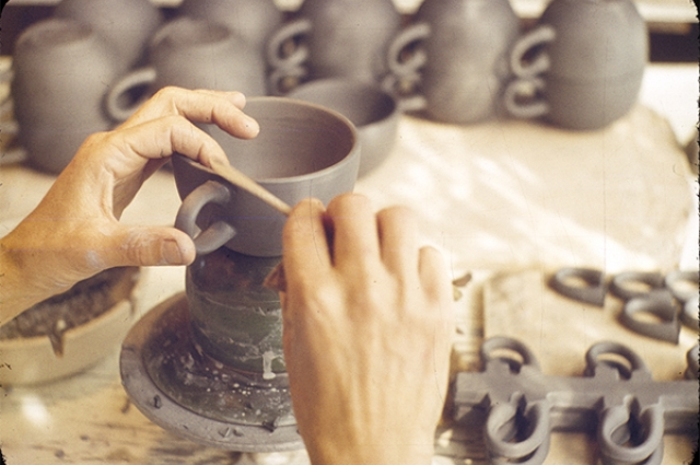Making a cup handle at pottery wheel
