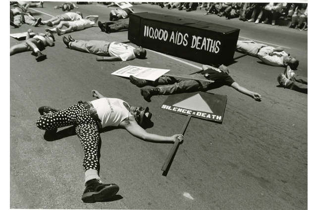 Black and white photo of many people lying on the ground with a platform that reads: 110,000 AIDS DEATHS