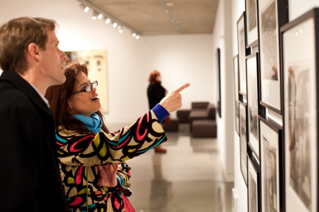 Man and women look at art, woman points to photograph