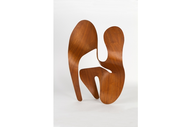Curved light brown plywood sculpture against a white background