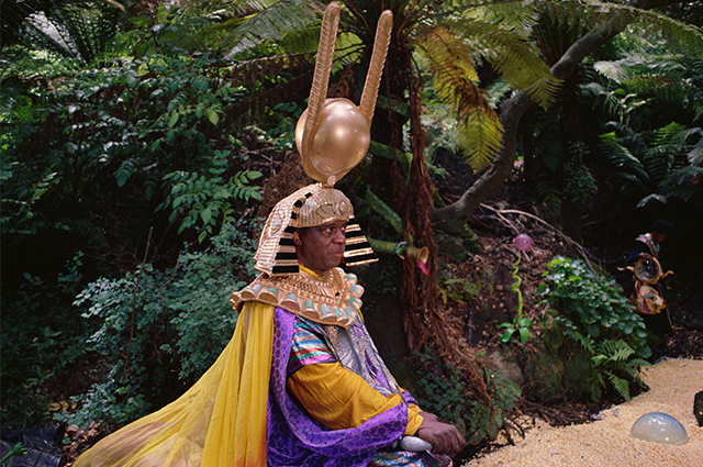 Sun Ra kneels on the ground, wearing a large intricate headpiece