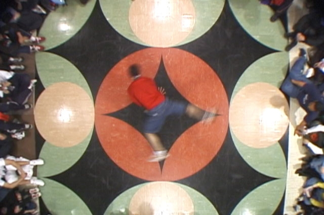 A b-boy dancing on a floor painted with a mandala. Still from video Sanford Biggers, Mandala of the B-Bodhisattva II, 2000 featured in RESPECT: Hip-Hop Style and Wisdom at the Oakland Museum of California.