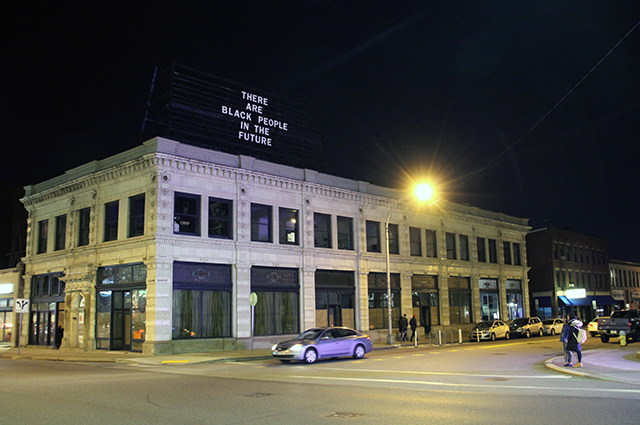 Photograph of building in Oakland at night with billboard above that says There Are Black People in the Future